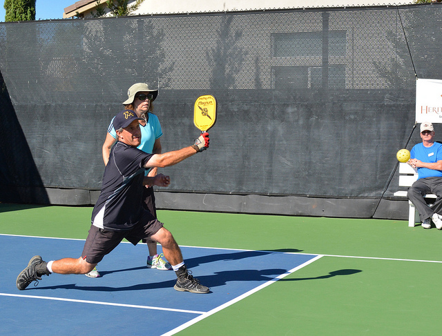 Man and woman playing pickleball outdoors