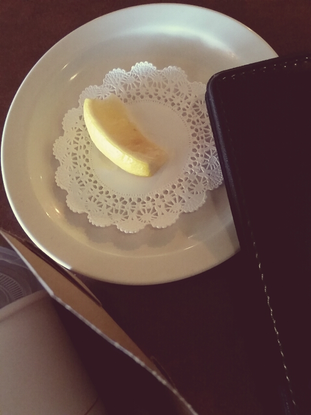 Plate with slice of lemon, takeout box and restaurant check folder lying on table.