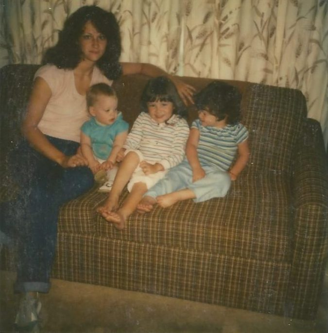 Mom and 3 children sitting on brown couch